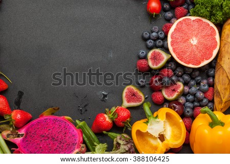 Vegetables and fruits, on the black background board - stock photo
