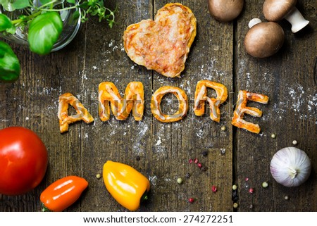Vegetables and spices on wood, pizza dough, heart, word Amore - stock photo