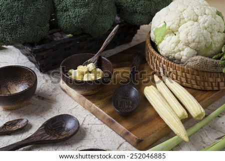 Vegetables and wooden bowl and wooden spoons on vintage wood background - stock photo