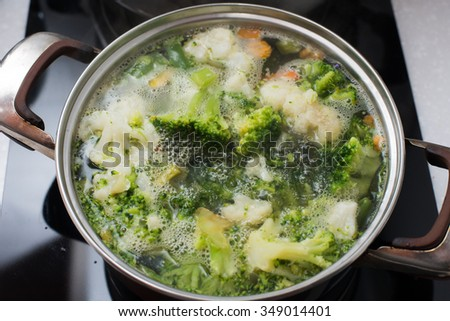 vegetables: broccoli, beans and carrots are simmered in a saucepan on electric tile