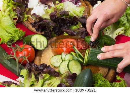 Vegetables, cucumber and tomato slicing with a knife for mixed salad, studio shot with hands for healthy food - stock photo