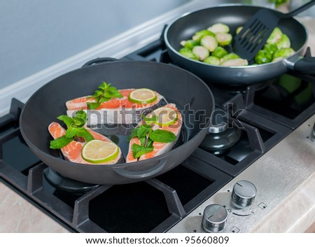 vegetables dish prepared in a black skillet in the kitchen - stock photo