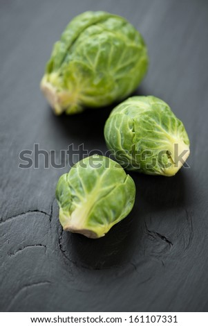 Vegetables: fresh brussels sprouts over dark wooden background - stock photo
