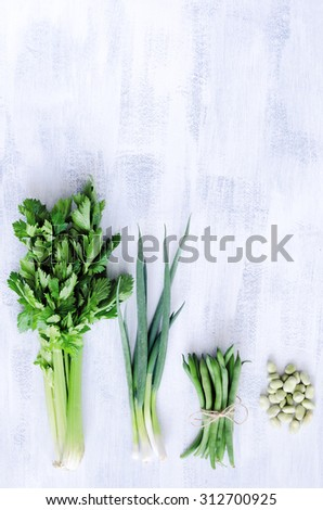 Vegetables from the farmers market on a white rustic background, celery spring onion beans shot from overhead