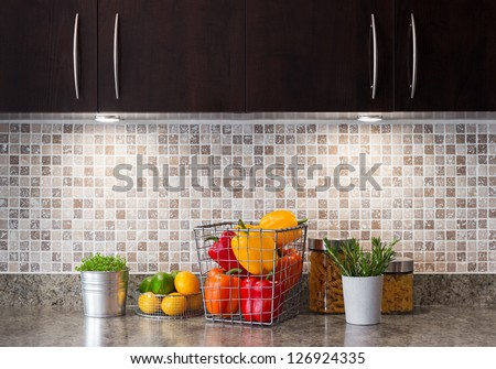 Vegetables, fruits and herbs in a contemporary kitchen with cozy lighting. - stock photo