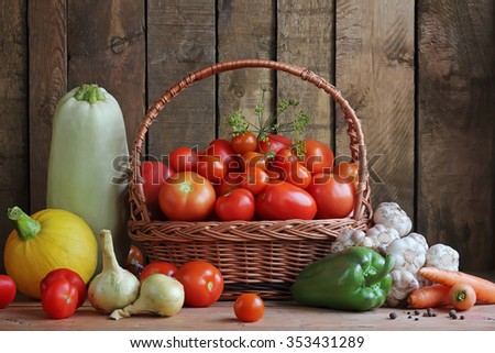 Vegetables in a basket: tomato, fennel, vegetable marrow, pumpkin, onions, pepper, garlic, carrots. Food, still life. Ripe red tomatoes in a basket and other vegetables against from boards. - stock photo