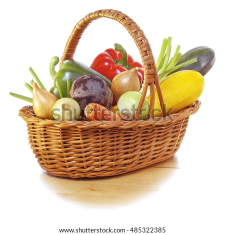Vegetables in basket on wooden table with a white background.