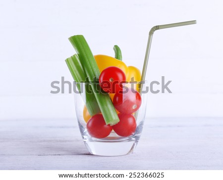 Vegetables in glass with tube on color wooden planks background