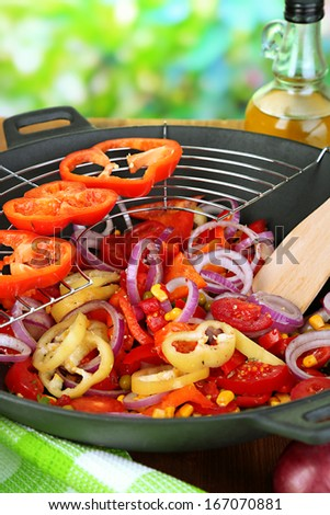 Vegetables in wok on wooden table on natural background - stock photo