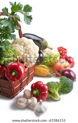 Vegetables. Mix of fresh ripe vegetables placed in a wicker basket and around isolated on white background - stock photo