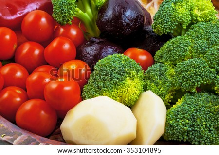 Vegetables on a plate. Broccoli, peeled raw potatoes, peeled boiled beets, red peppers, cherry tomatoes - stock photo