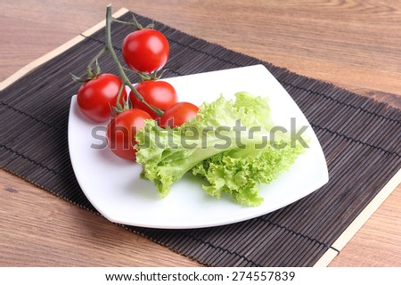 Vegetables on a square plate. Organic vegetables. The cherry tomatoes on a branch. Red tomatoes on a branch, lettuce. Diet food. Dieting, weight lose. Delicious and healthy lunch. The veggie platter. - stock photo