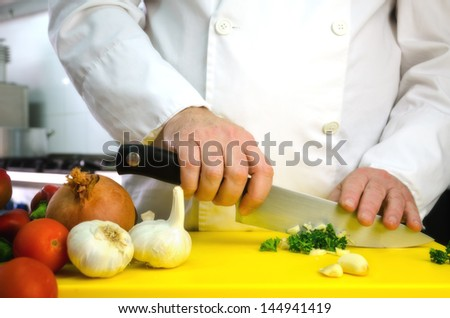 Vegetables on cutting board and chef hands detail, restaurant kitchen on background