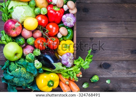 Vegetables on rustic wood background, text space. - stock photo