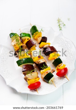 vegetables on skewer with peppers, zucchini, mushrooms, eggplant and cherry tomatoes  in ceramic dish on rustic white planks - stock photo
