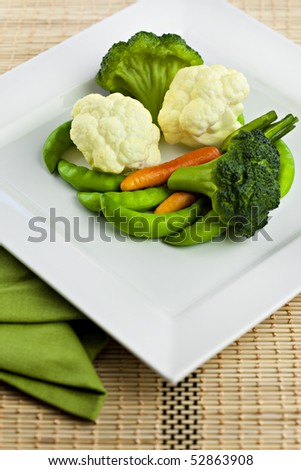 Vegetables On White Plate With Bamboo Placemat and Napkin - stock photo