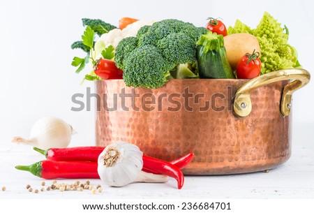 Vegetables on white rustic background.Winter veggies, broccoli, cauliflower,romanesco broccoli, carrots, potatoes,onion, tomatoes, kale, chile peppers, garlic. - stock photo