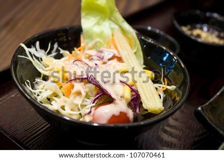 Vegetables salad in black bowl at restaurant - stock photo