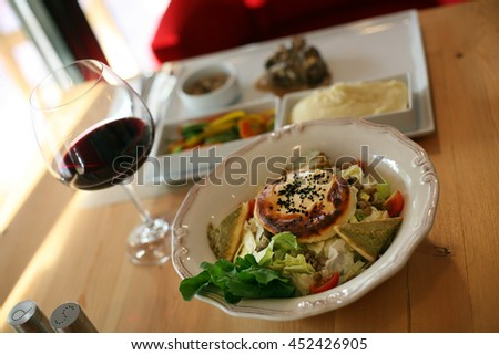 Vegetables salad, pastry, beefsteak, appetizer food with red wine on the restaurant table. - stock photo