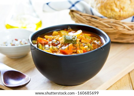 Vegetables soup with chickpea by bread loaf - stock photo