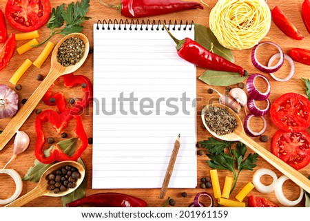 Vegetables, spices and recipes notepad on wooden cutting board. - stock photo