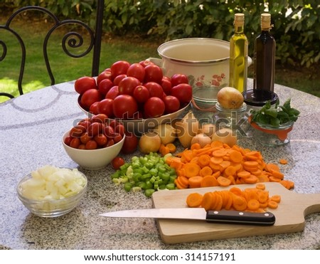 Vegetables, tomatoes, onions, chopped celery, carrot and basil leaves on the table with bottles of olive oil and balsamico vinegar. Preserving jars, cooking pot. Cooking of italian style tomato sauce. - stock photo