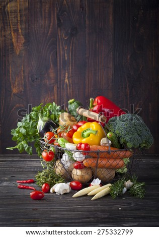 Vegetables variety in a wire basket on a wooden background. Copy space - stock photo
