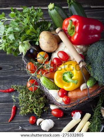Vegetables variety in a wire basket on a wooden background. Healthy food - stock photo