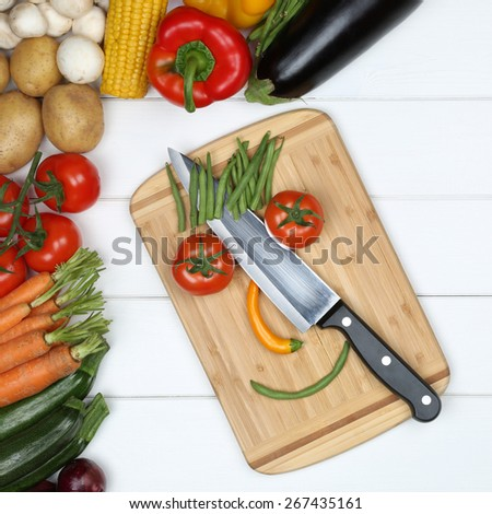Vegetarian and vegan eating smiling face from vegetables on cutting board with knife - stock photo