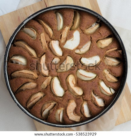 Vegetarian apple cake in a baking pan on a wooden board, top view