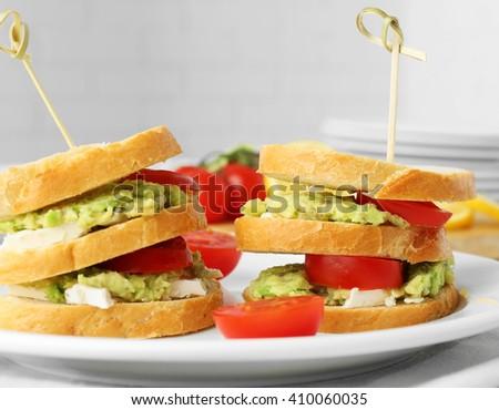 Vegetarian avocado sandwich on a white plate. - stock photo