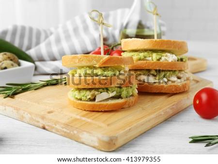 Vegetarian avocado sandwiches on a wooden board. - stock photo