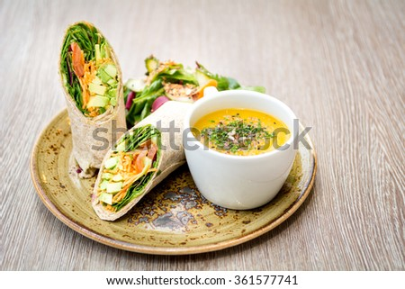 vegetarian avocado tortilla wrap sandwich and cup of decorated soup on rustic plate - stock photo