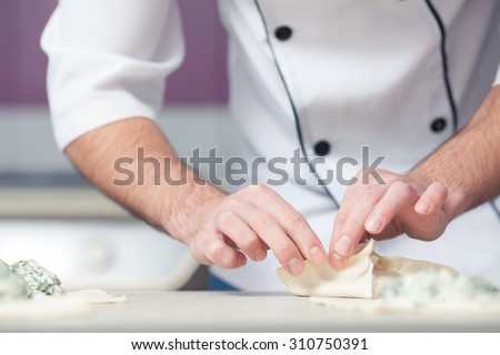 Vegetarian bakery concept. Chef cook in uniform putting filler of spinach and soft feta cheese on slice of puff pastry and making french chausson. Close up. Indoor shot - stock photo