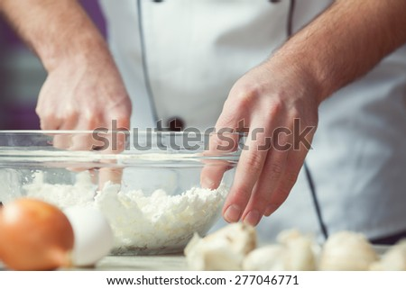 Vegetarian bakery concept. Chef's hands mixing feta cheese and eggs in kitchen of cafe, restaurant. Close up. Indoor shot - stock photo