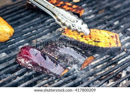 Vegetarian barbecue with eggplant seasoned with olive oil, garlic and herbs. Grilled vegetables preparing on a barbecue grill over charcoal. Aubergine or eggplant, sliced and grilled on bbq. - stock photo