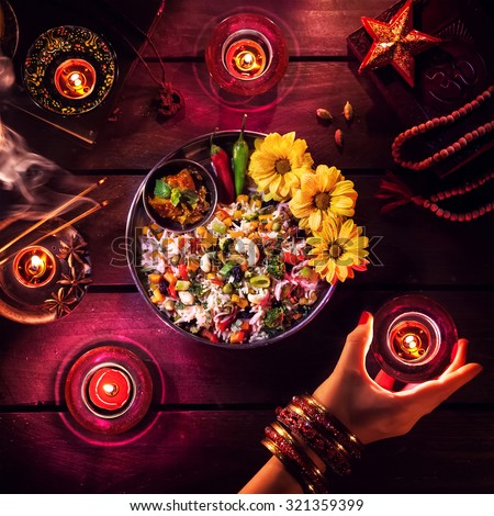 Vegetarian biryani, candles, incense and religious symbols at Diwali celebration on the table - stock photo
