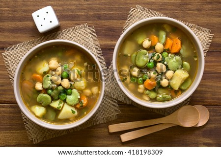 Vegetarian chickpea soup with carrot, broad bean (fava bean), pea, potato, onion, garlic and parsley served in bowls, photographed overhead on wood with natural light