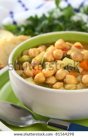 Vegetarian chickpea soup with carrots, potatoes, onions and leek (Selective Focus, Focus on the row of chickpeas in the front of the soup)