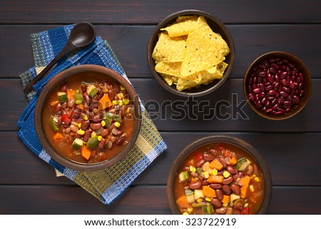 Vegetarian chili dish with kidney bean, carrot, zucchini, bell pepper, sweet corn, tomato, onion, garlic, tortilla chips and raw kidney beans on the side, photographed on dark wood with natural light - stock photo