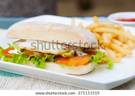 Vegetarian Ciabatta with tomatoes, grilled cheese haloumi, avocado and lettuce with french fries on white plate Summer background