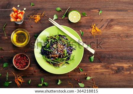 Vegetarian concept. Salad of raw vegetables on a green plate. Products for quick weight loss. A balanced menu of vegetables such as cabbage, carrots, arugula. Space for writing a text - stock photo