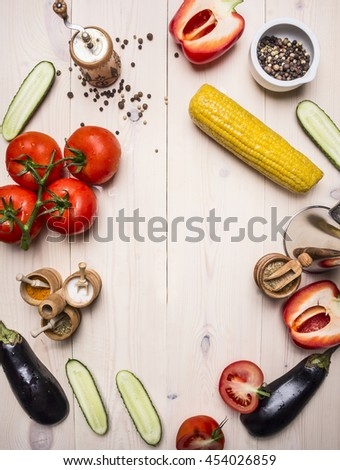 vegetarian concept tomatoes, whole pepper, red bell pepper, corn, cucumbers and seasonings on wooden rustic background top view close up