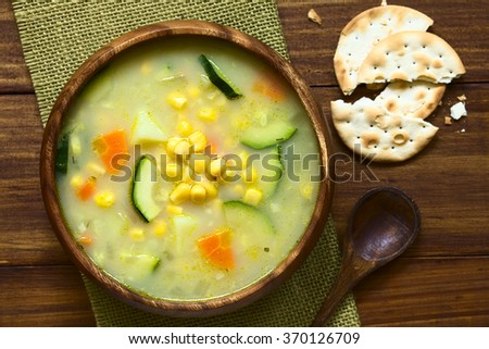 Vegetarian corn and courgette chowder served in wooden bowl, saltine cracker and wooden spoon on the side, photographed overhead with natural light (Selective Focus, Focus on the top of the soup) - stock photo