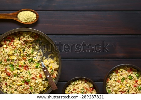 Vegetarian couscous salad made with bell pepper, tomato, cucumber, red onion and sweet corn kernels, raw couscous on wooden spoon on the top. Photographed overhead on dark wood with natural light. - stock photo
