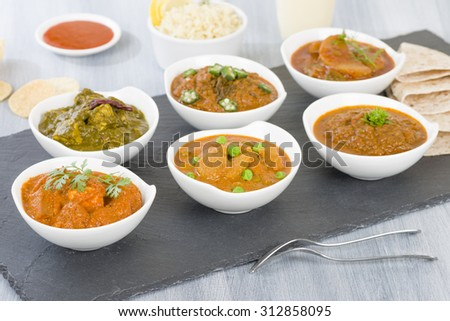Vegetarian Curries - Selection of South Asian vegetarian curries in white bowls. Paneer Makhani, Palak Paneer, Aloo Matar, Baigan Bharta, Chilli Potatoes and Bhindi Masala.
