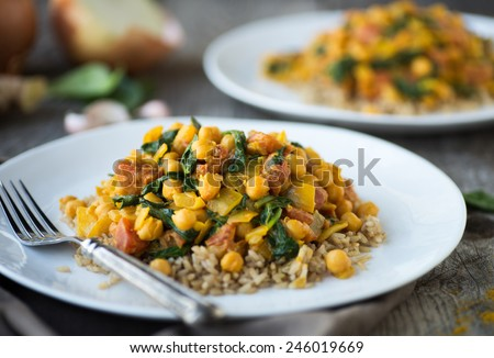 Vegetarian curry dish with chickpeas tomatoes and spinach over brown rice - stock photo