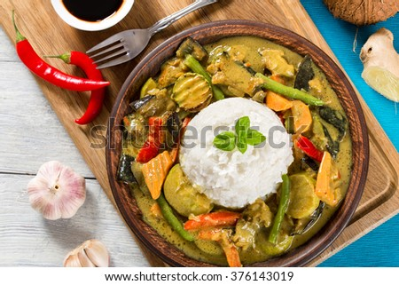 vegetarian curry with rice on a clay brown dish on a wood cutting board with coconut, ginger and soy sauce top view - stock photo