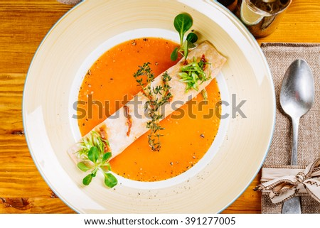 Vegetarian delicious vegetable soup with vegetable puree peppers, pumpkin and carrot  soup puree with spices  in bowl on the wooden background. vegetarian diet, cooking, culinary and food concept. - stock photo