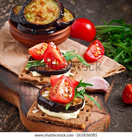 Vegetarian Diet Crispbread sandwiches with garlic cream cheese, roasted eggplant, arugula and cherry tomatoes on old wooden background - stock photo